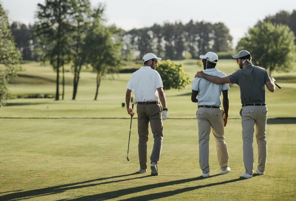 Three golf players in conversation while walking on a golf course