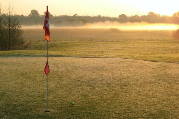 Ball near a golf hole on a golf course during sun set