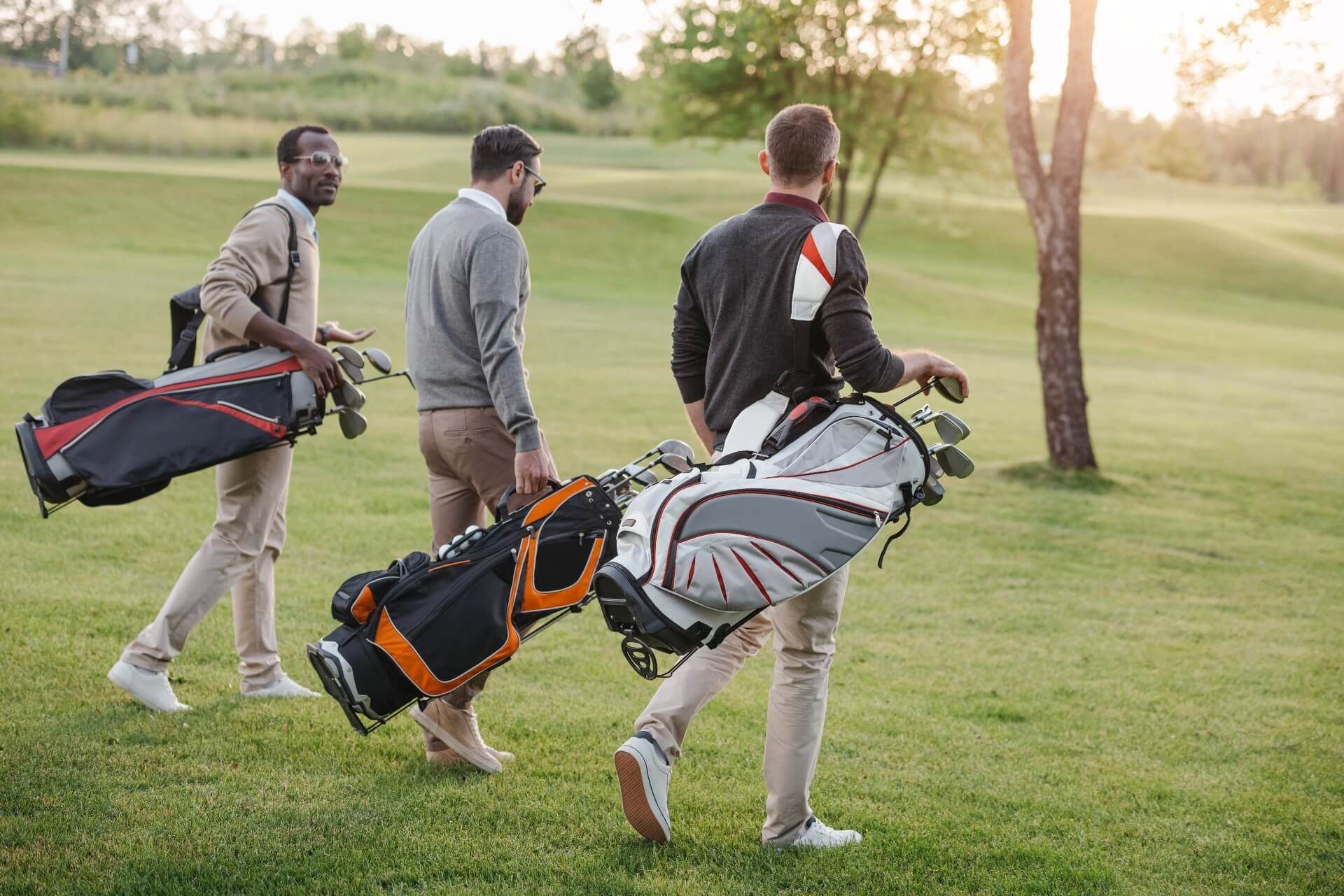 Three golf players walking with their golf tour bags on a golf course