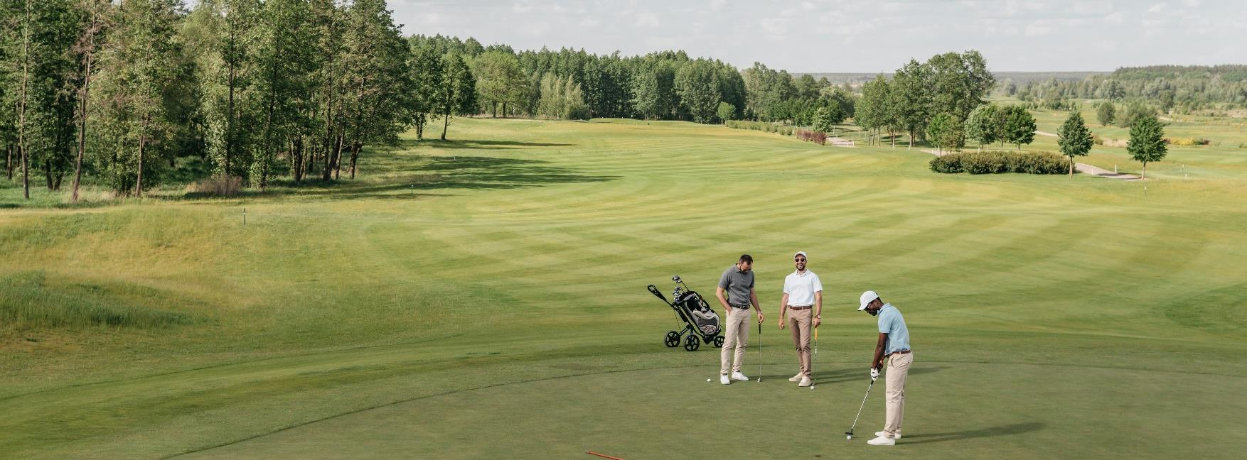 Picture of three golf players on a green playing golf