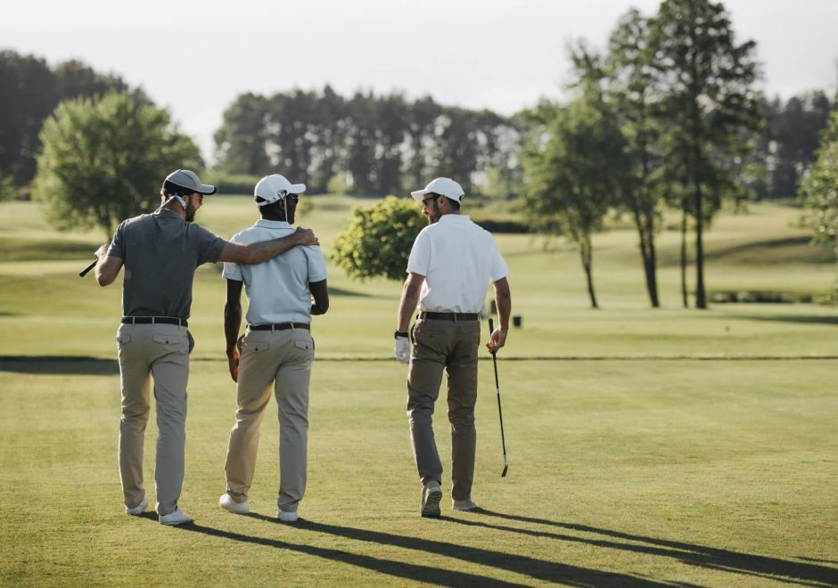 Three golf players walking with their golf clubs on a golf course