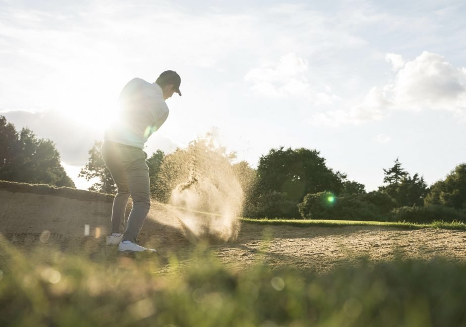 A person swinging at a golf ball on a sand pit under cloudy skies