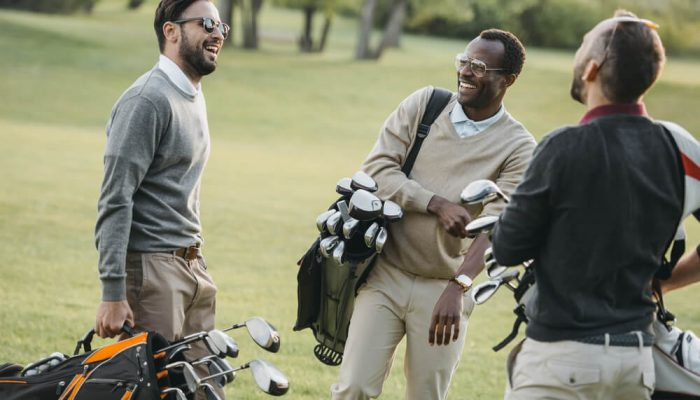 Three golf players with their golf tour bags in conversation
