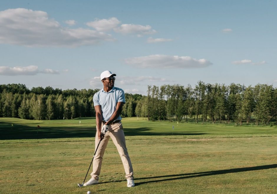 Picture of a man about to swing at a golf ball on a golf course